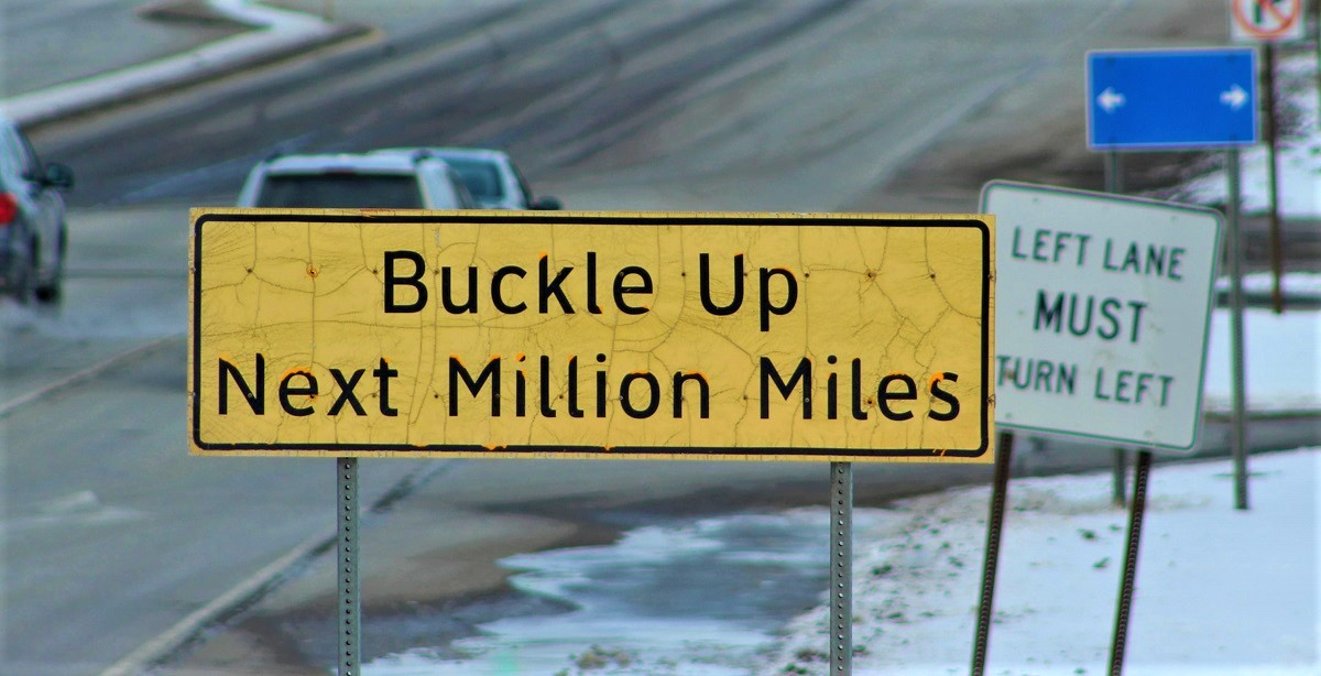A sign saying Buckle Up Next Million Miles