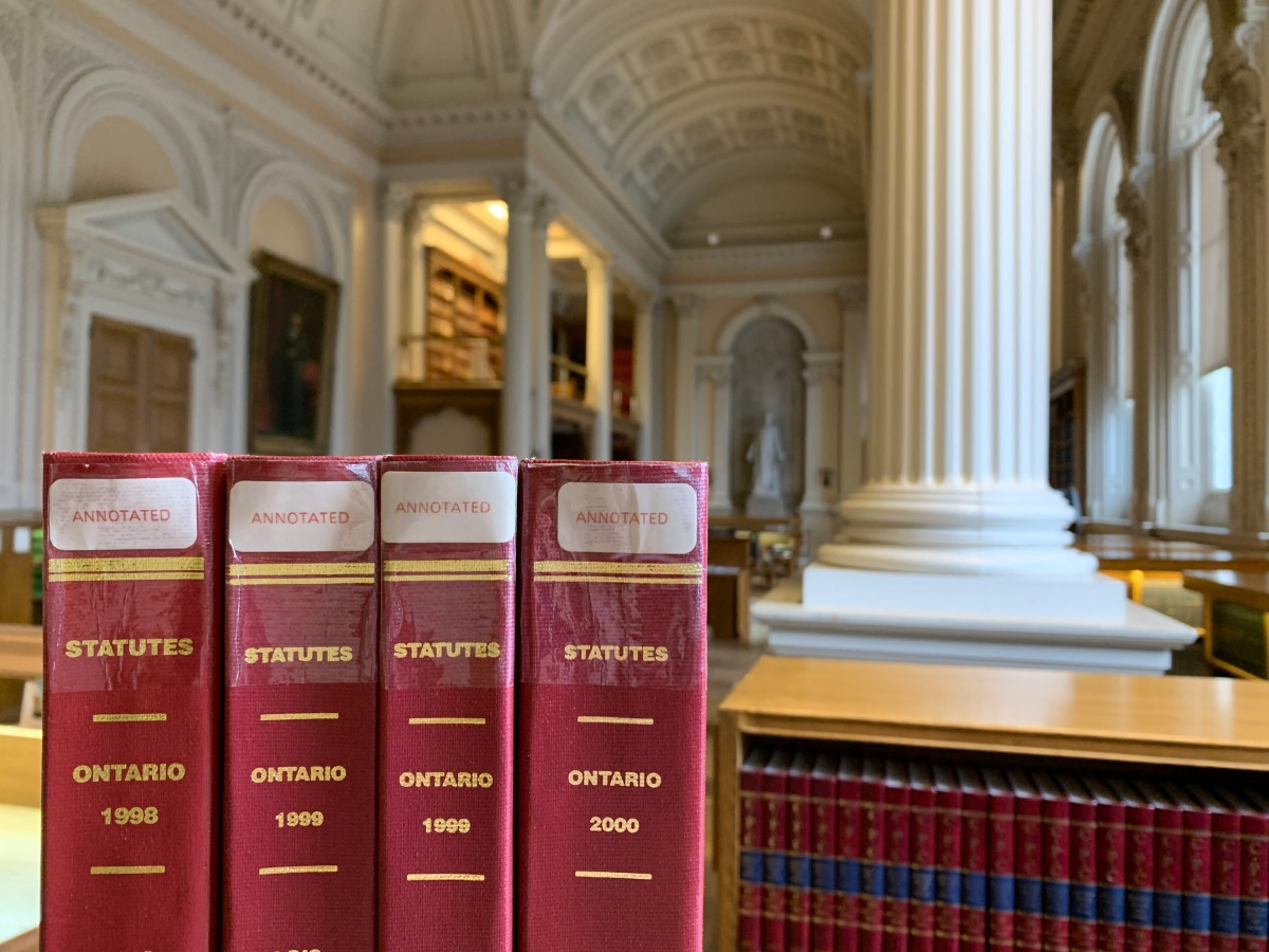 Four annotated Statutes of Ontario volumes with the Great Library in the background