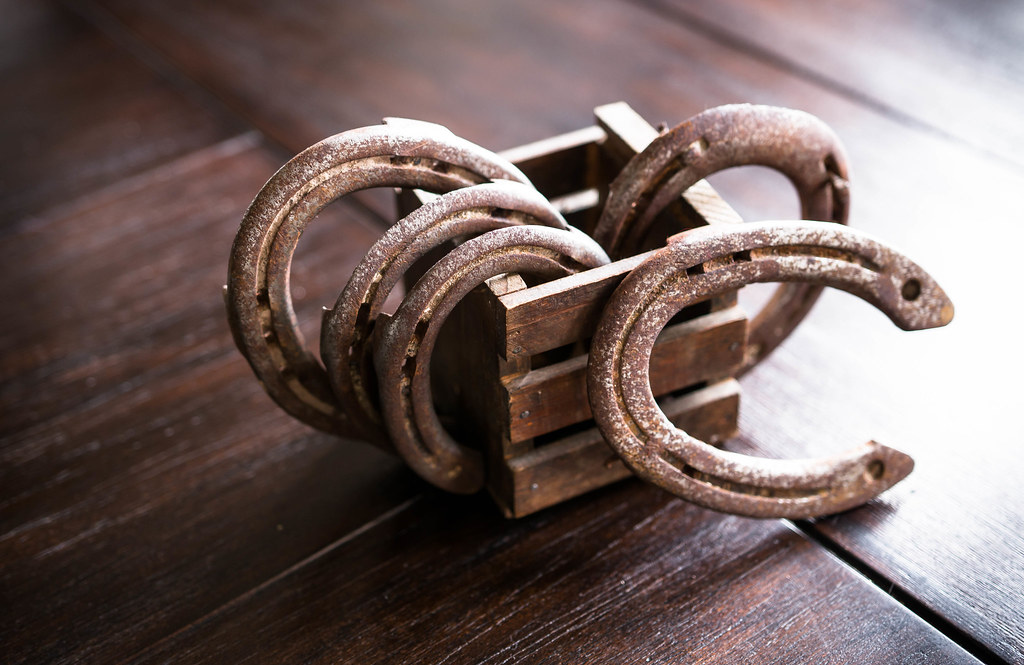 A picture of five rusty horseshoes in a small wooden box.
